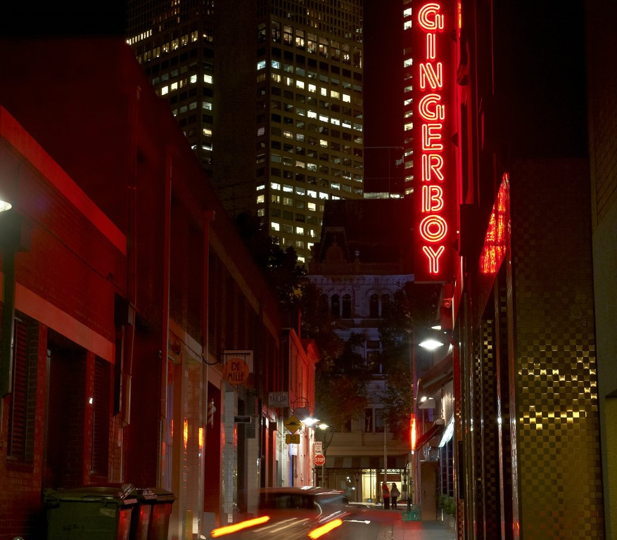 A neon sign lit up in a laneway at night