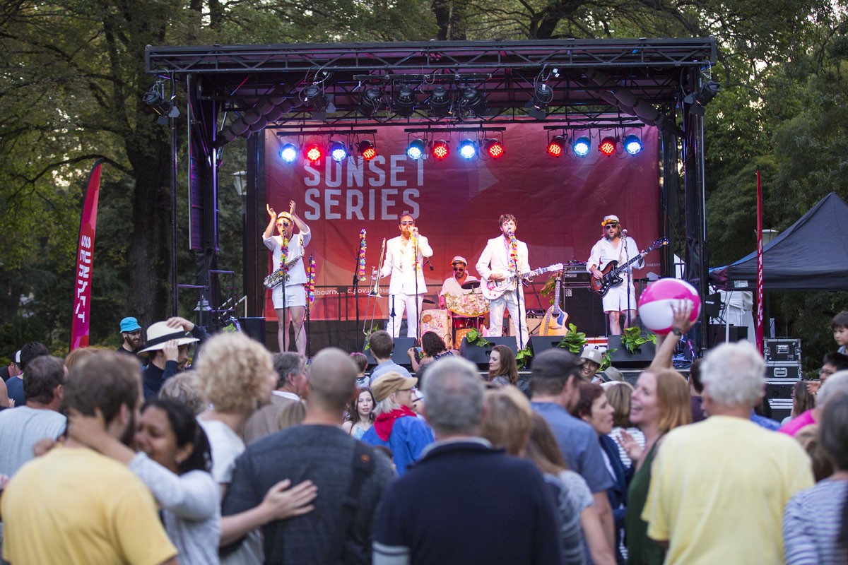 Four men in white stand on a stage playing musical instruments in front of a large crowd.