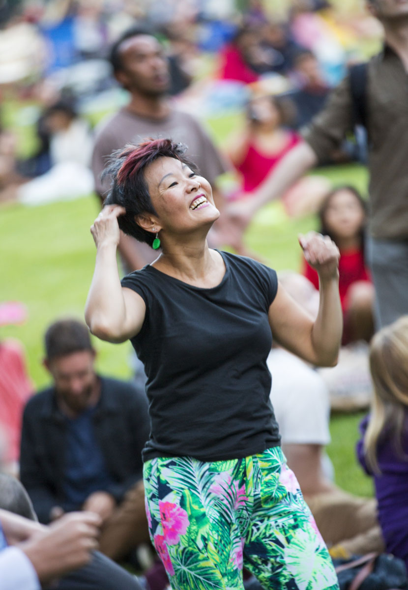 A woman wearing a black top and a green skirt dances.