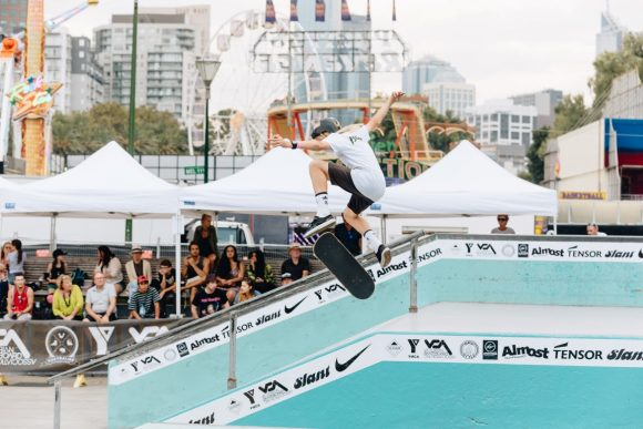 A man leaping high in the air on a skateboard with a crowd of people watching