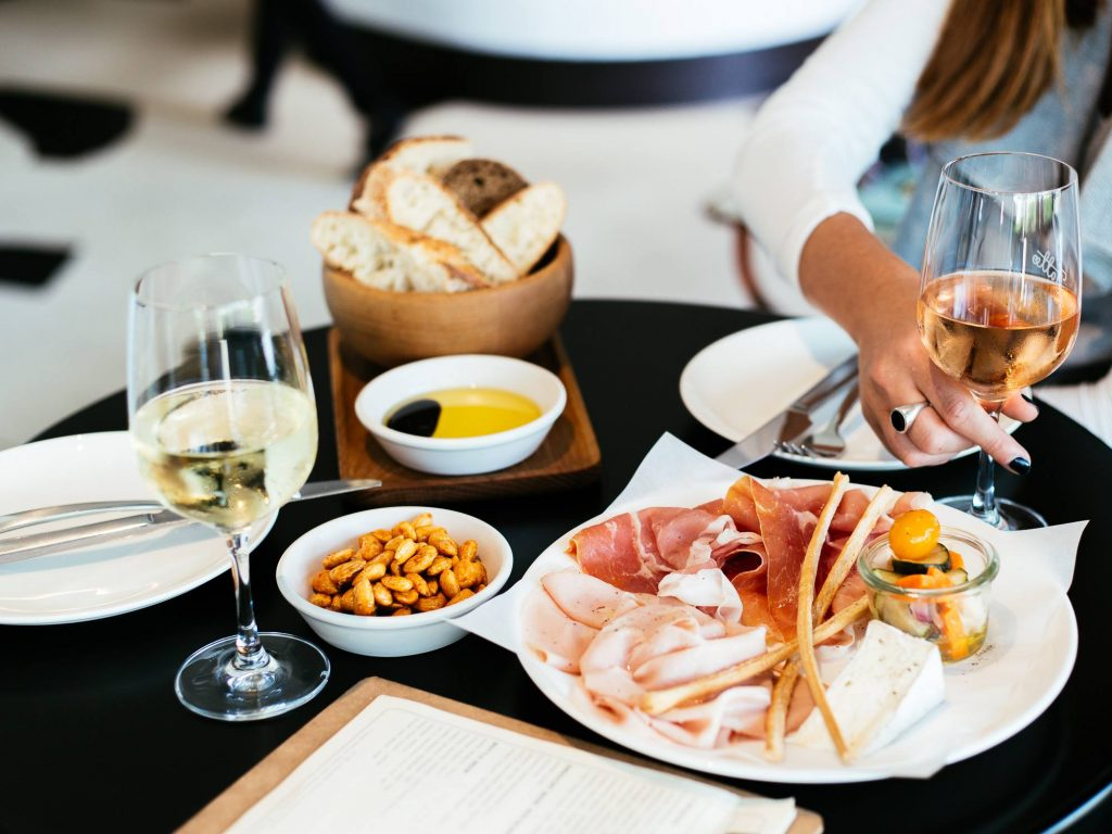 A restaurant table with plates of bread and cured meat, a bowl of peanuts, and two glasses of wine. A ladies hand is holding one of the glasses.