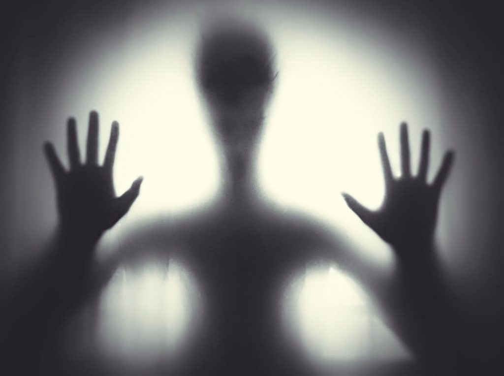 A ghostly figure standing in front of a light