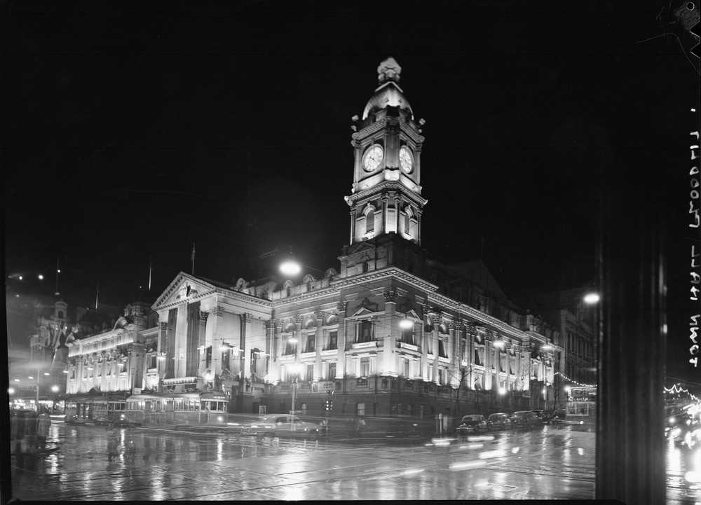 An old photograph of an old building lit up at night