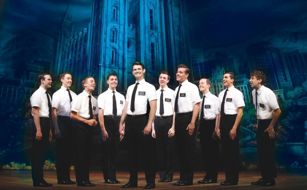 Ten men in white shirt and black pants standing on a stage