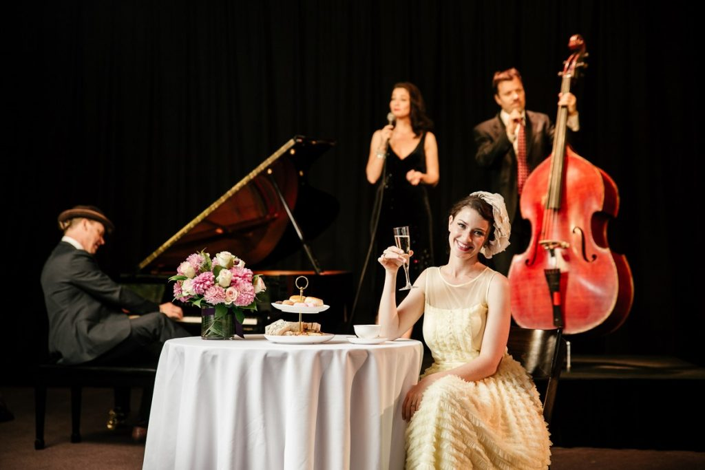 A man in a black suit playing a grand piano, a women singing and a man playing cello and a women holding a glass in a white dress smiling