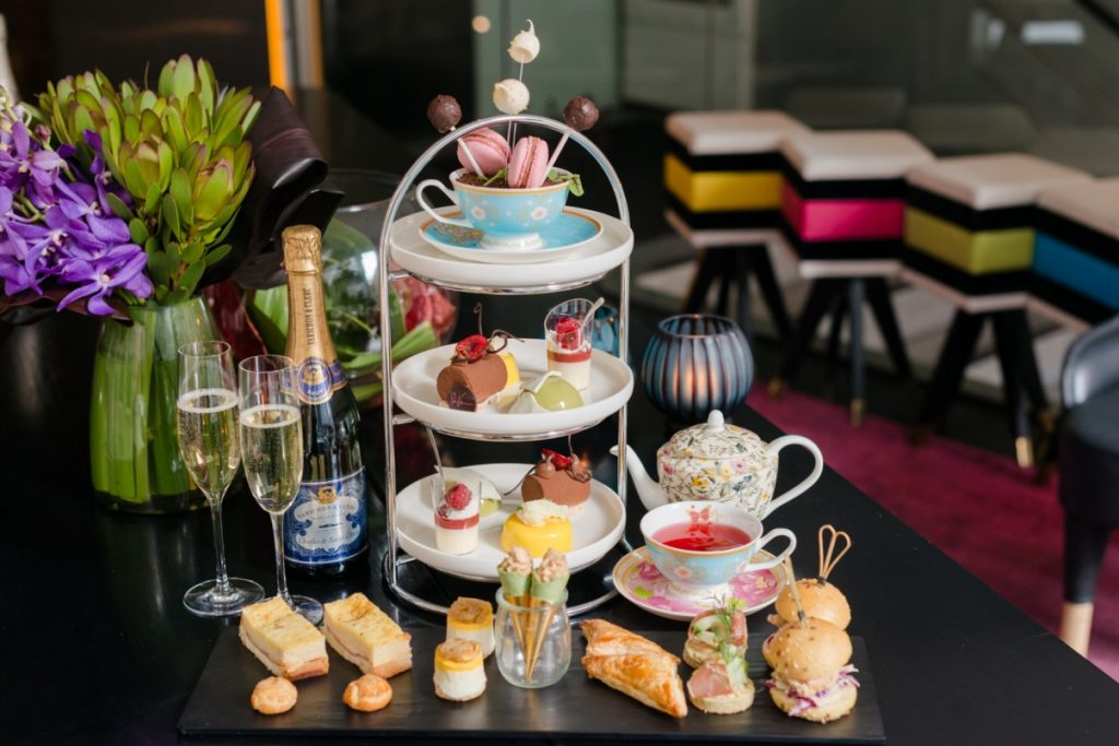 A table of sweet treats, champagne, and a tea pot and a cup