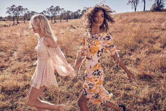 Two women holding hands wearing summer dresses.