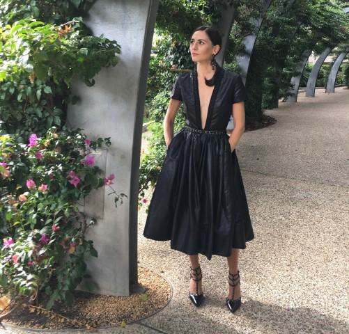 Woman wearing black evening dress with black high heels posing outside near flower garden.