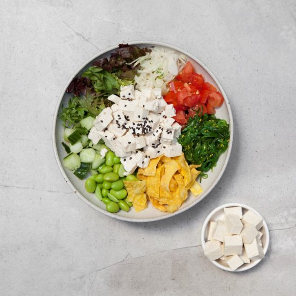 Bowl of brightly coloured tofu poked on a grey table. Bowl is filled with tofu, salad, beans, tomatoes and other vegetables.