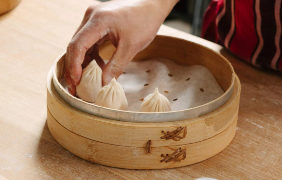 A hand putting a dumpling into a steamer with other dumplings