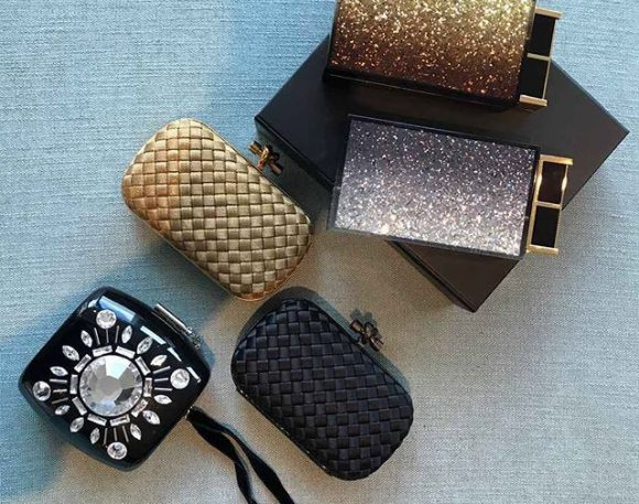A collection of black, silver and gold women's purses.