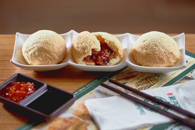 Three pork buns on a table with chopsticks