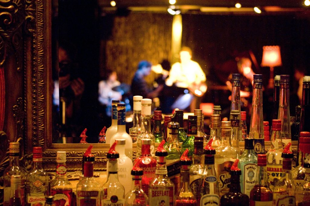 A group of spirit bottles at a bar, behind te bottles is a mirror and reflection of a band playing