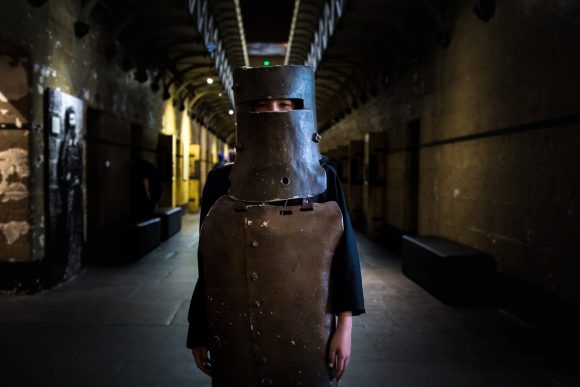 A person in a jail wearing a metal mask resembling the bushranger Ned Kelly.