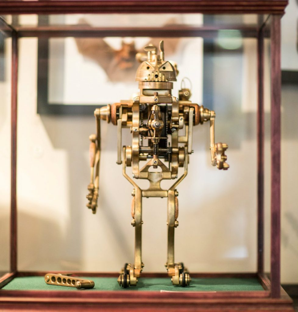A smal metal robot in a glass display case