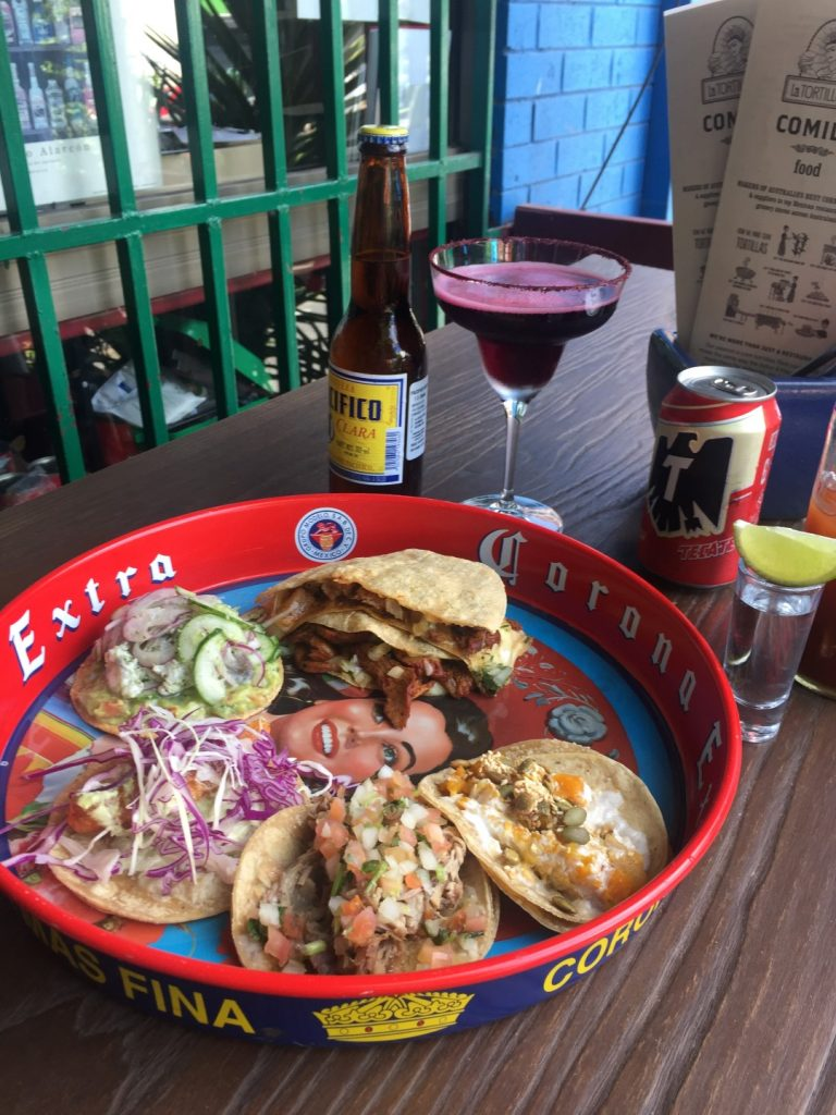 A plate of different tacos with a cocktail and a beer behind it, on a table