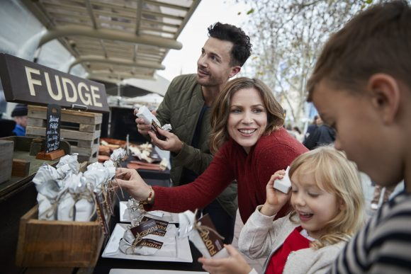 A woman, man and two children browsing a stall at an outdoor market