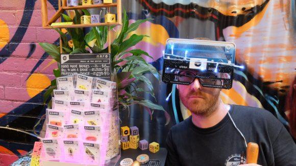 A man wearing high tech glasses next to a market stall