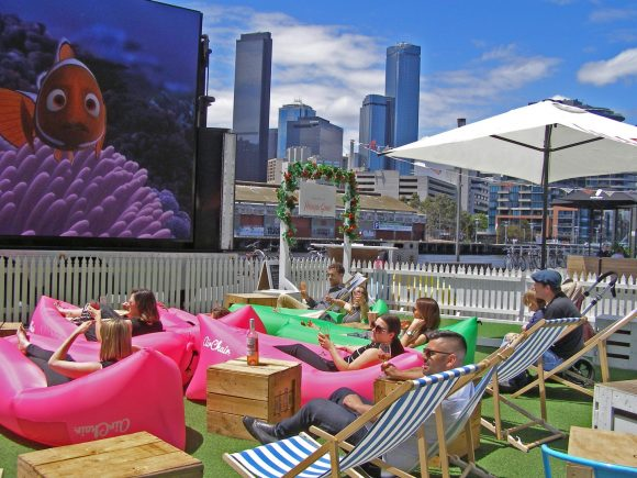 People sitting in bean bags and deckchairs watching a film outside with a river and the city skyline in the background