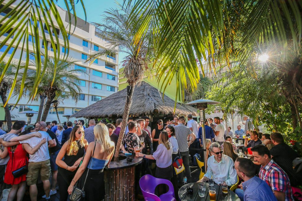 A group of people in a crowded rooftop bar surrounded by tropical plants