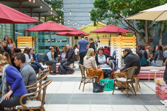 People sitting and drinking at outdoor tables in a courtyard