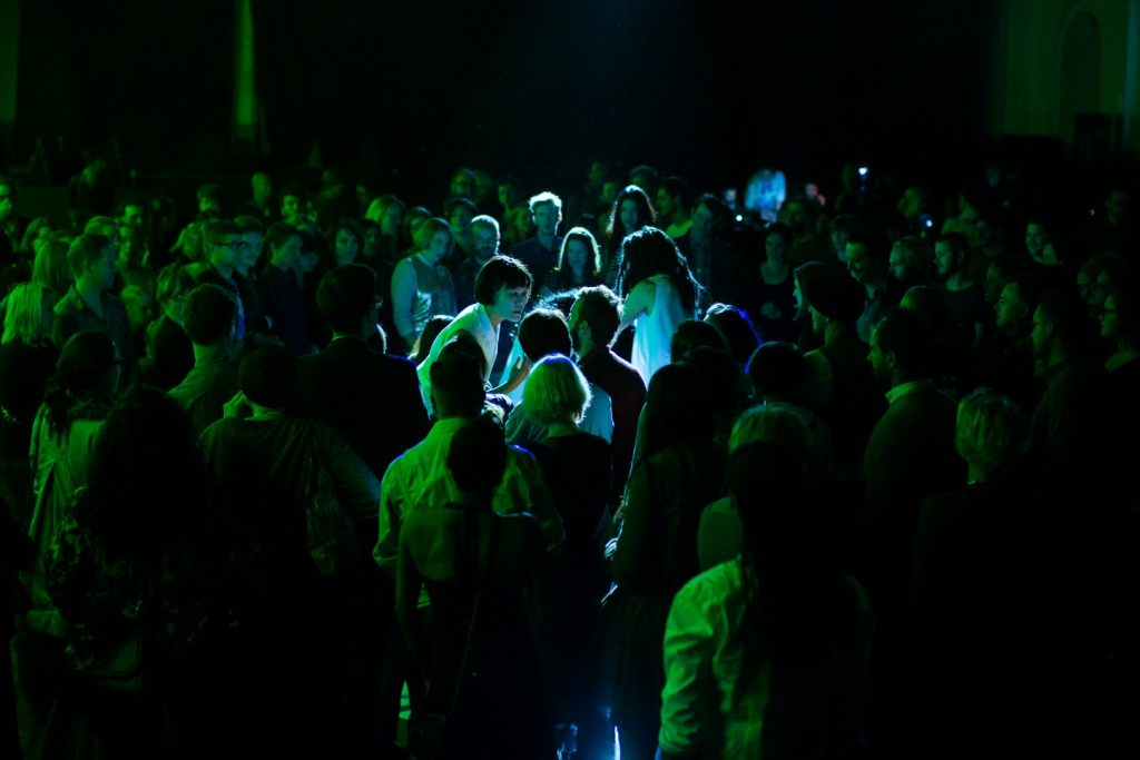 A dimly lit festival venue with people dancing bathed in green light