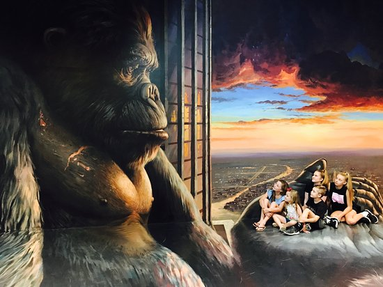 A painting of a gorilla on a wall, and a group of people crouched against the wall making it look like they are in the Gorilla's hand.