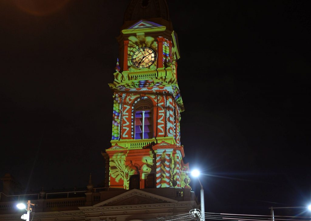 An historic building with multi-coloured projections on the side