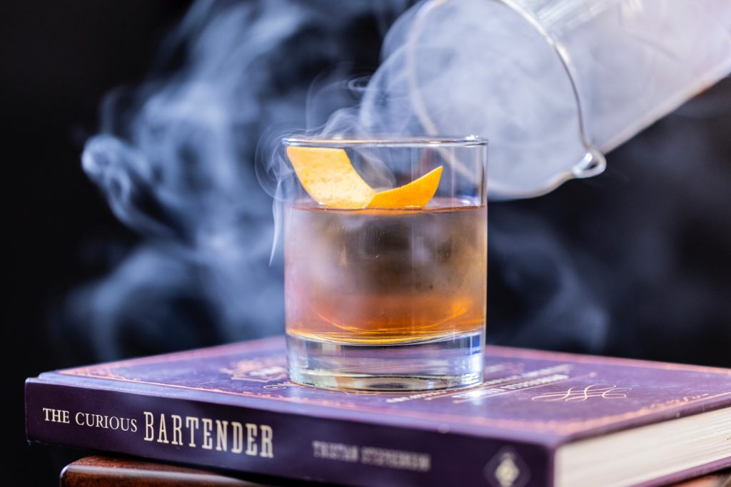 A short glass filled with amber liquid on a stack of books, with a plume of smoke over the top of the glass