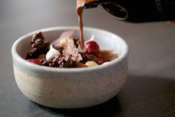 A bowl filled with fruit, chocolate flakes and cereal with chocolate milk poured over it