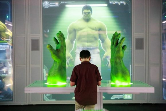 a boy standing in front of a exhibit of a monster man on a screen and two giant hands