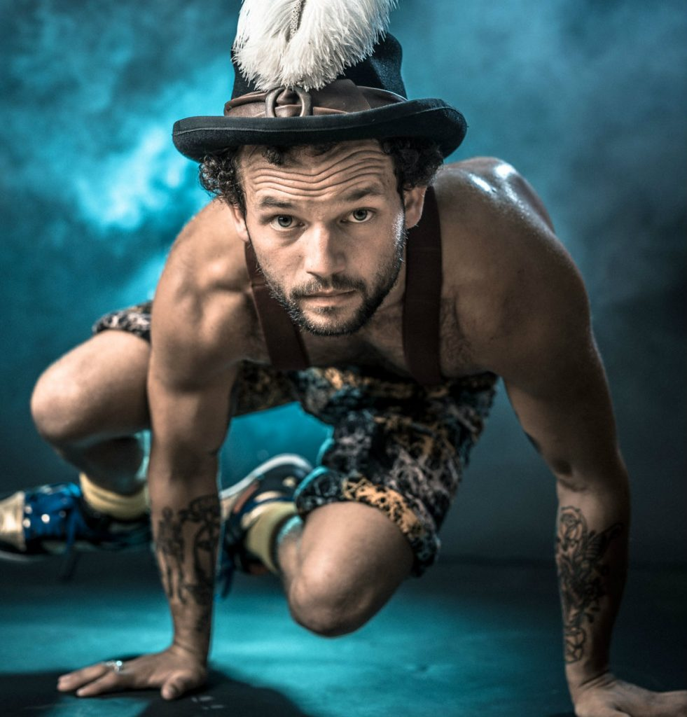 A man balancing on his hands looking at the camera. He is wearing a hat with tattoos on his arms.
