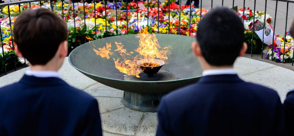 A flame burning in a metal container. Two people are standing with their backs to the camera looking at it.
