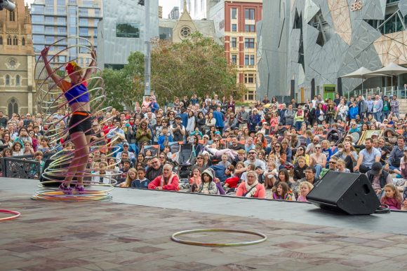A woman juggling hoops over a body in front of a crowd of people in a city square