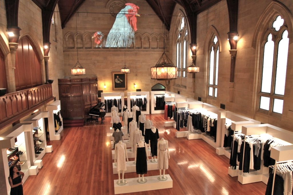 Clothes shop inside a churchlike room with high ceilings and a baby grand piano