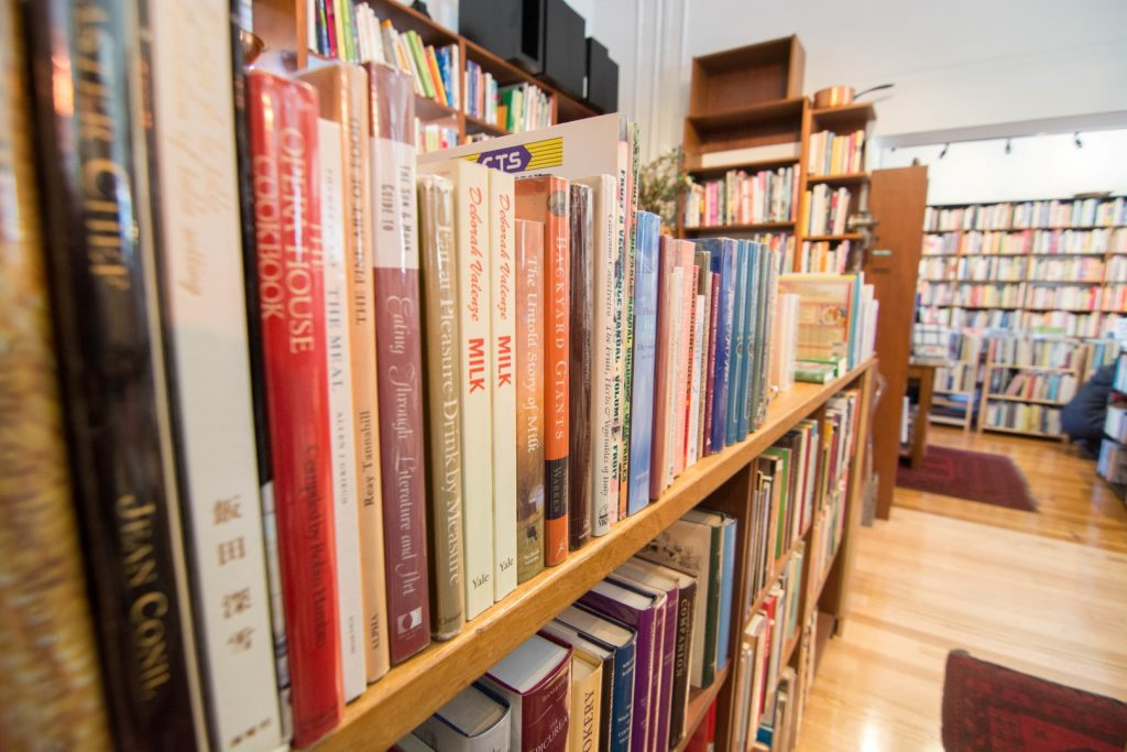 Side view of bookshelves filled with old and new cookbooks