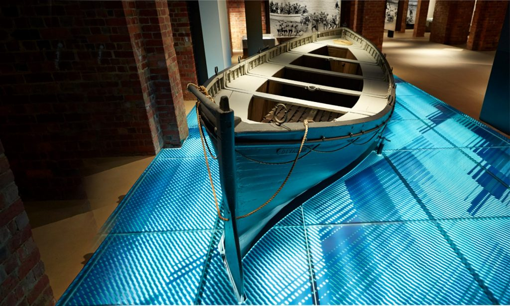 A wooden paddle boat on display in a gallery