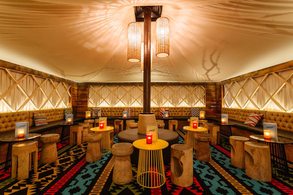 The interior of a bar which is made to look like a glamourous tent. There are several tables and stools in the picture.