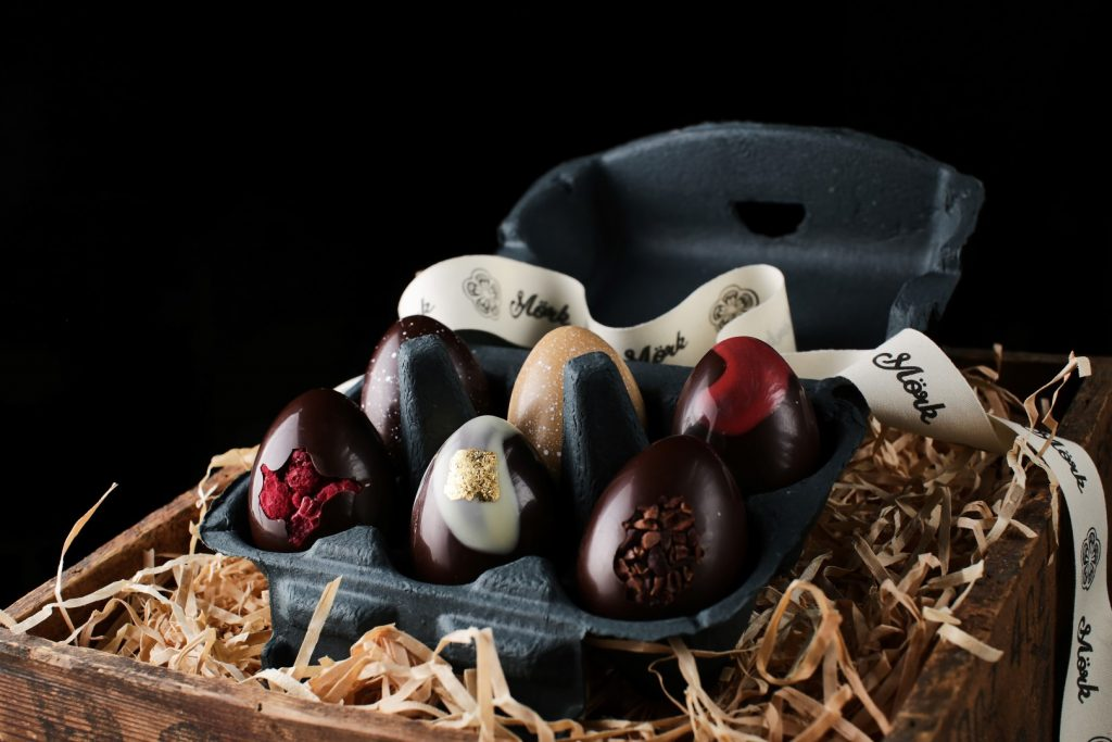 A range of marbled chocolate easter eggs in a black carton, placed on a bed of hay in a wooden crate