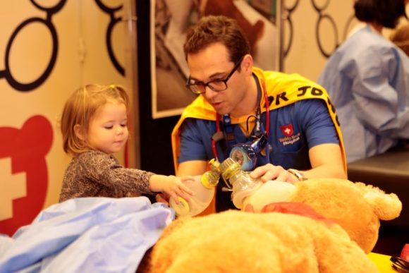A man dressed in a superhero costume playing with a little girl behind a teddy bear