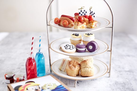 brightly coloured cakes and snacks on a high tea display stand with soda bottles and a box with Mickey Mouse design on the front
