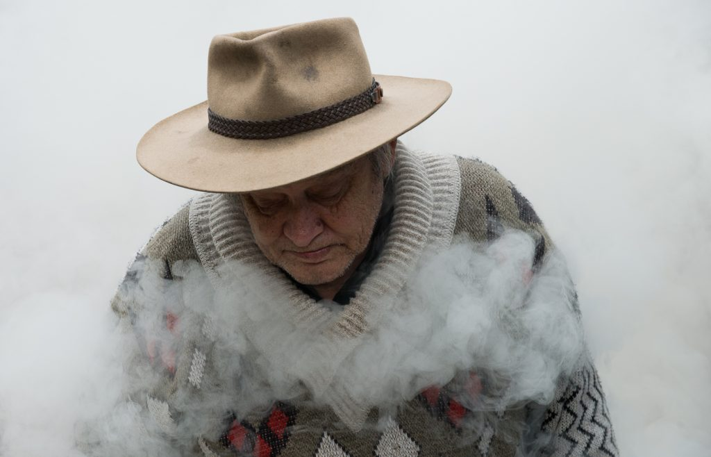 An old man surrounded by mist and looking down with his etes closed.