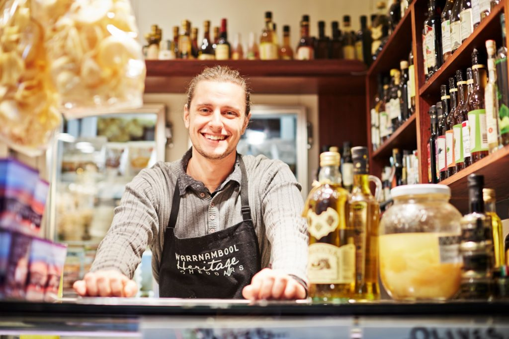 A man is leaning on a market stall counter and smiling.