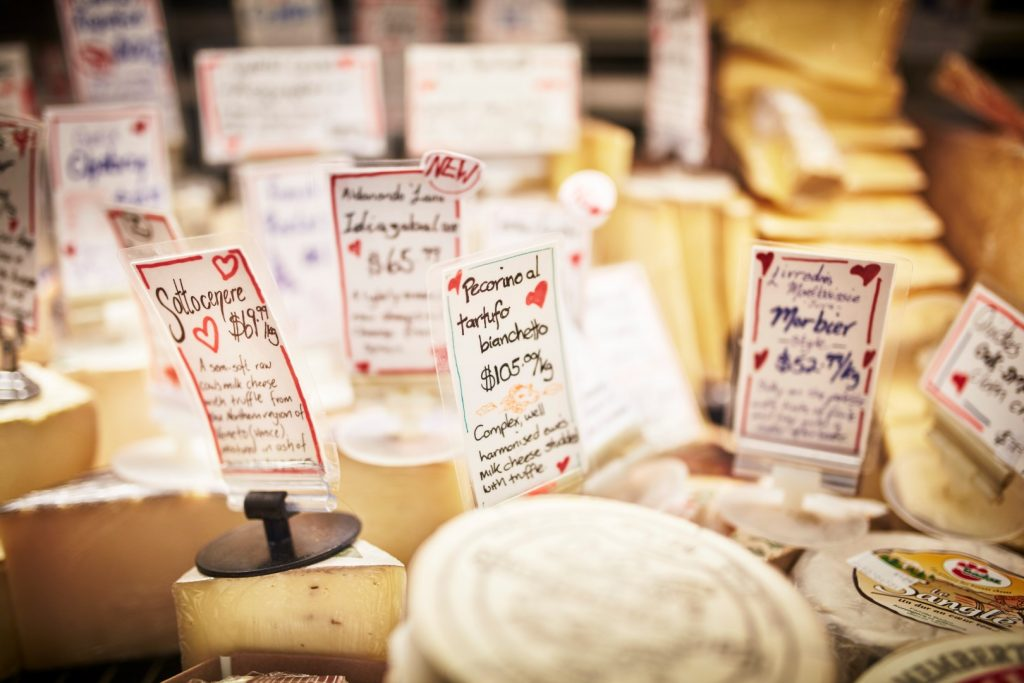 A market stall displaying many different cheeses.