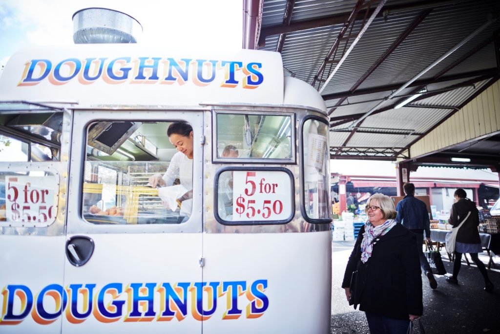 A van with the word doughnuts written on it. A woman is inside preparing food for a customer who is waiting.