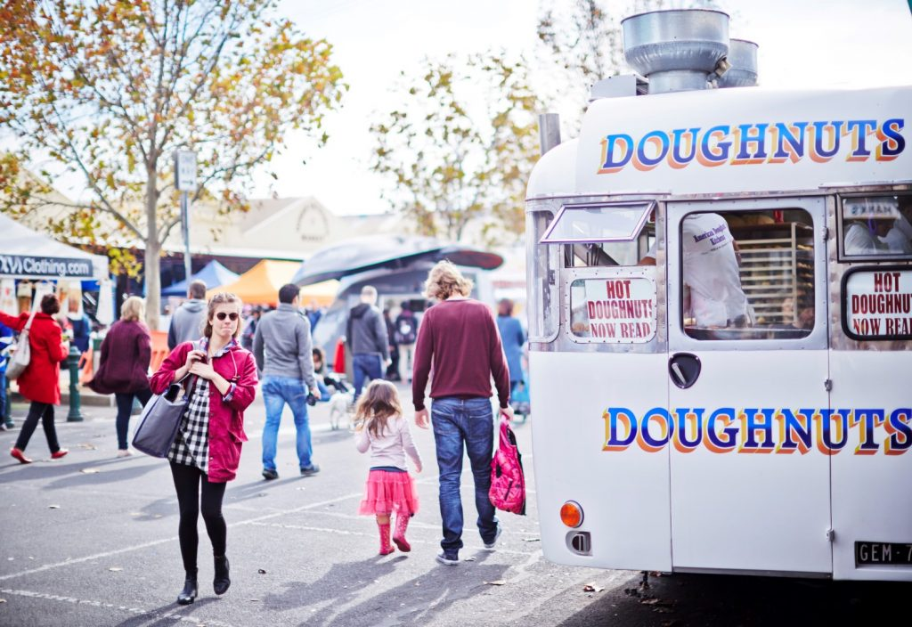 Image of white doughnut van outdoors on street surrounding by people.