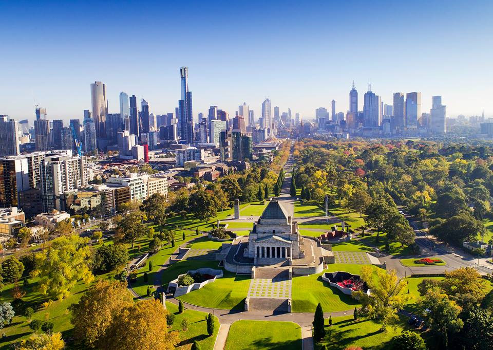 A view of an old monument surrounded by parks with the city skyline in the background