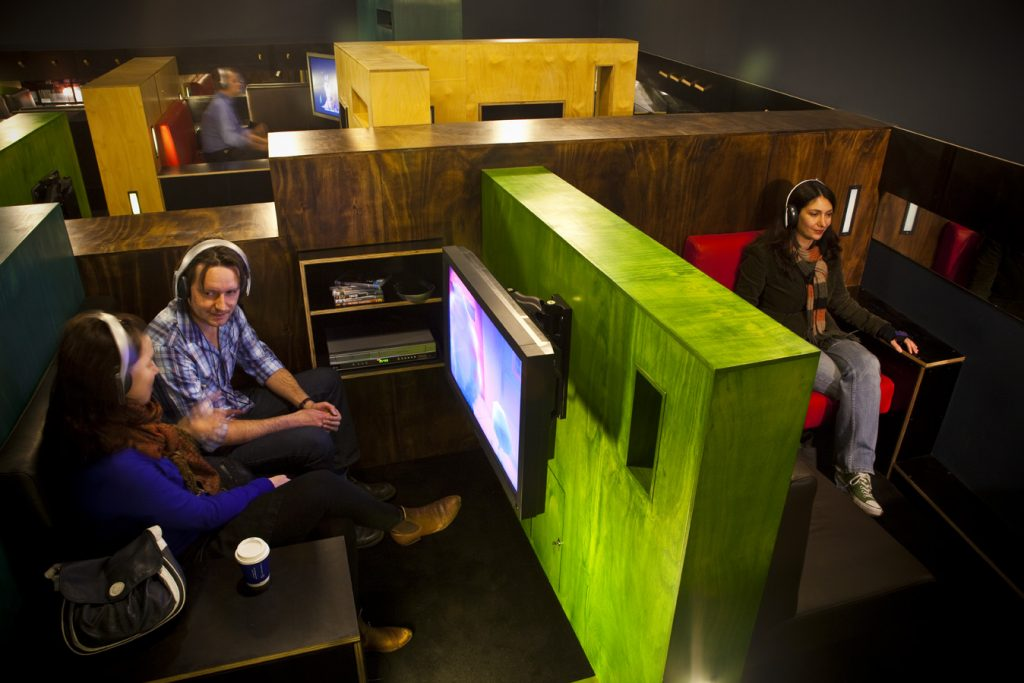 Two people sitting in a booth with headphones on watching a video