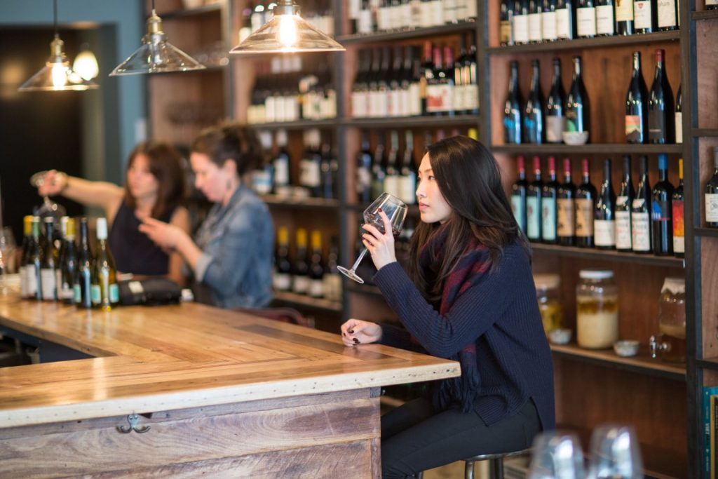 Woman sipping a red wine at a bar seating, with a wine store in the background