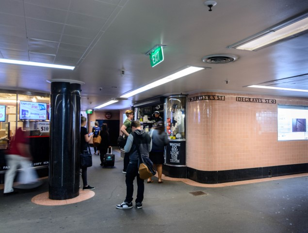 A people walking through a subway underpass past a tiny cafe